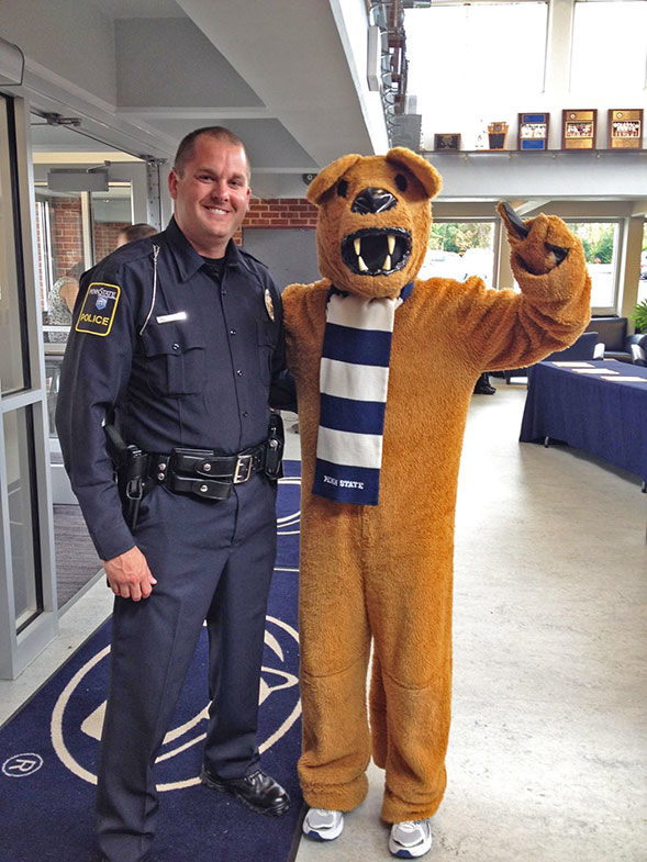 Public Safety Manager, Wesley Sheets poses with the Penn State New Kensington lion mascot at the entrance to the Athletic Center