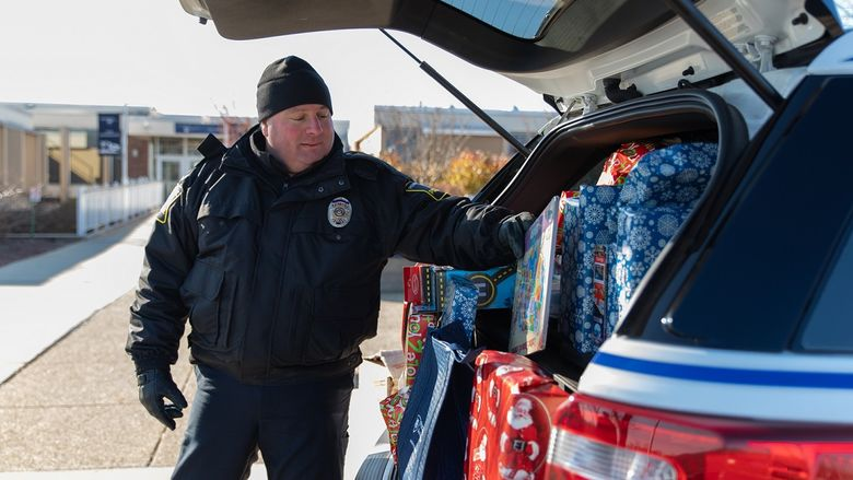 Police officer puts gift in car