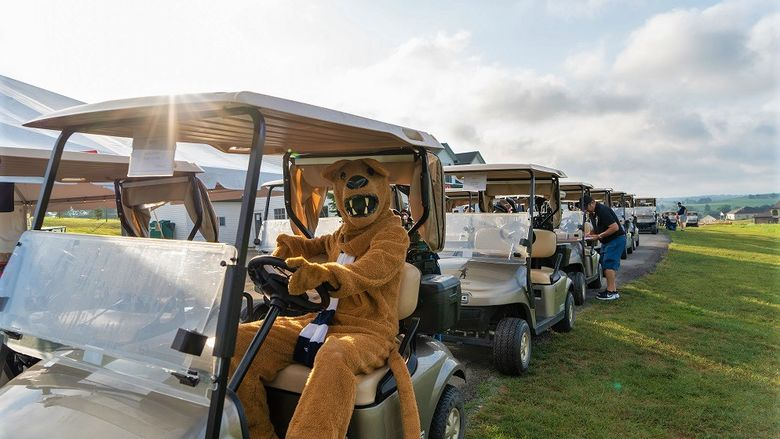 Nittany Lion mascot sits in golf cart