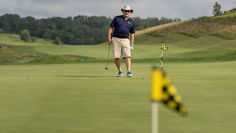 Man watches golf ball on green after putt
