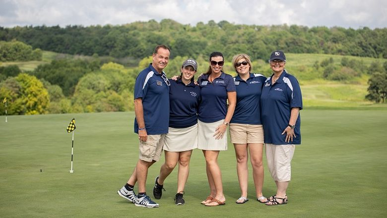 Men and women pose for photo on golf course green