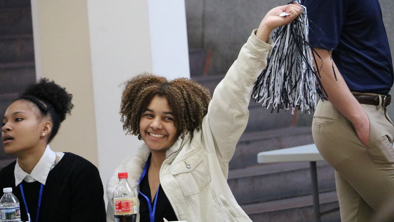 Student smiles and waves pom-pom