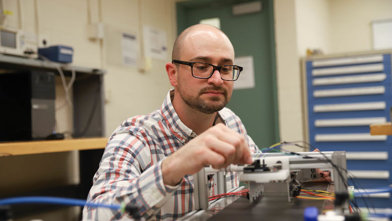 Joseph Cuiffi wiring conveyor belt in lab