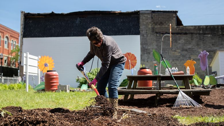 Woman shovels mulch at community garden