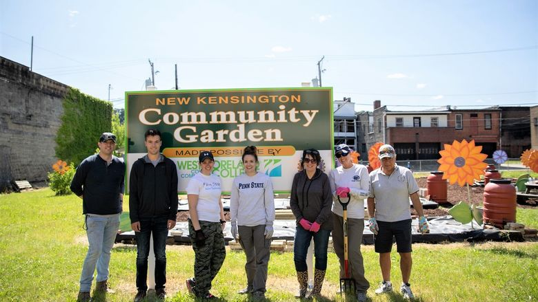 Seven men and women stand in community garden