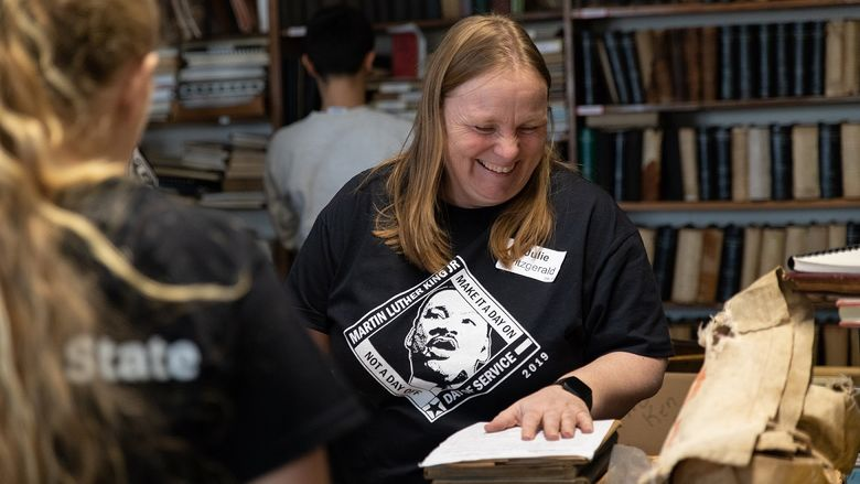 Woman moves books while smiling