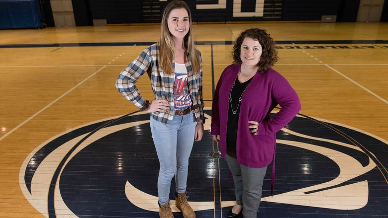 Two women standing in middle of gymnasium floor