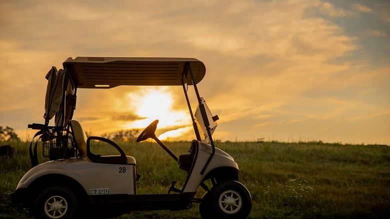 Sunrise behind golf cart on golf course