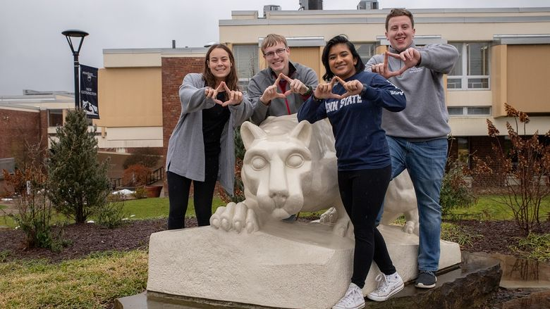 Four students stand by lion statue