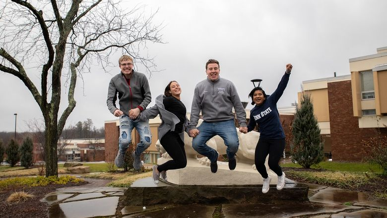 Four students jump in the air