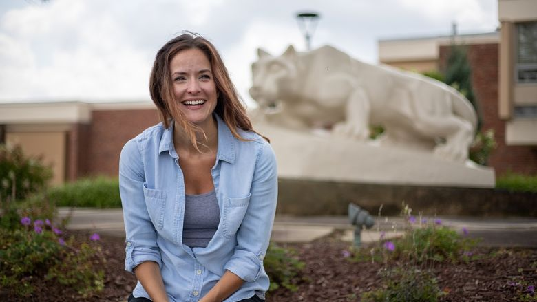 Woman sits in front of Nittany Lion Shrine