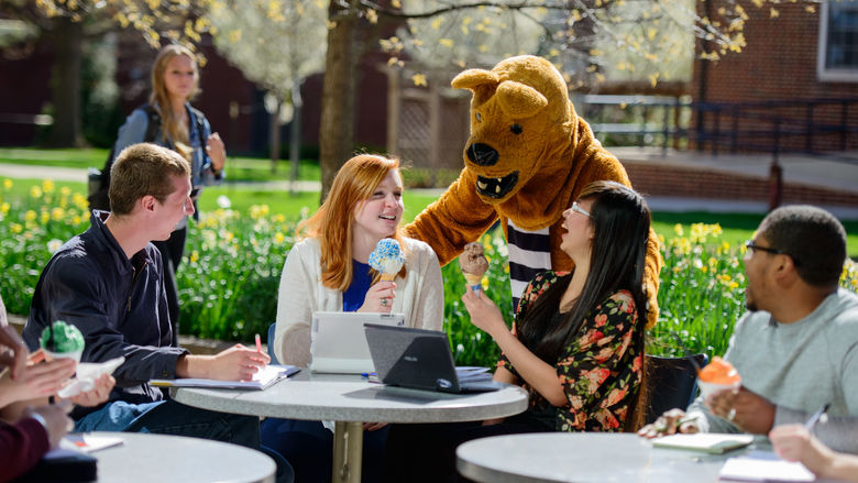 Lion mascot with four students sitting at table