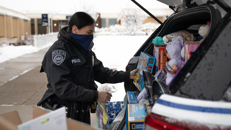 Police officer loading police cruiser with donated items