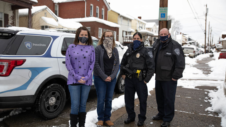 Four individuals stand outside wearing masks