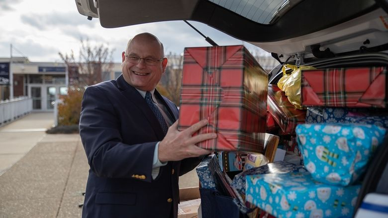 Man puts wrapped gift in car