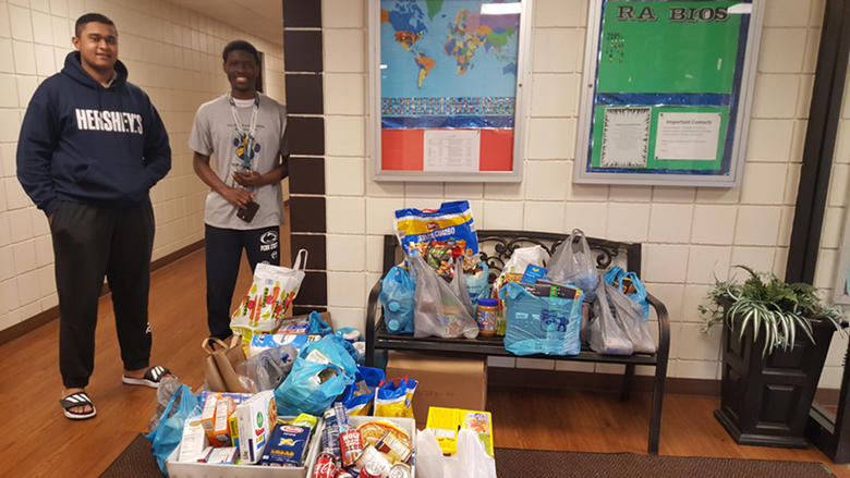 Two students stand by donated food and paper products