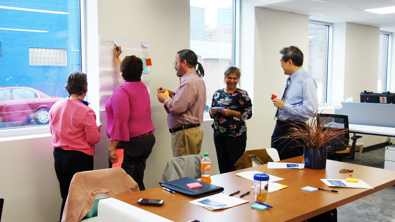 Faculty and staff posting notes on a large sheet of paper hanging on wall