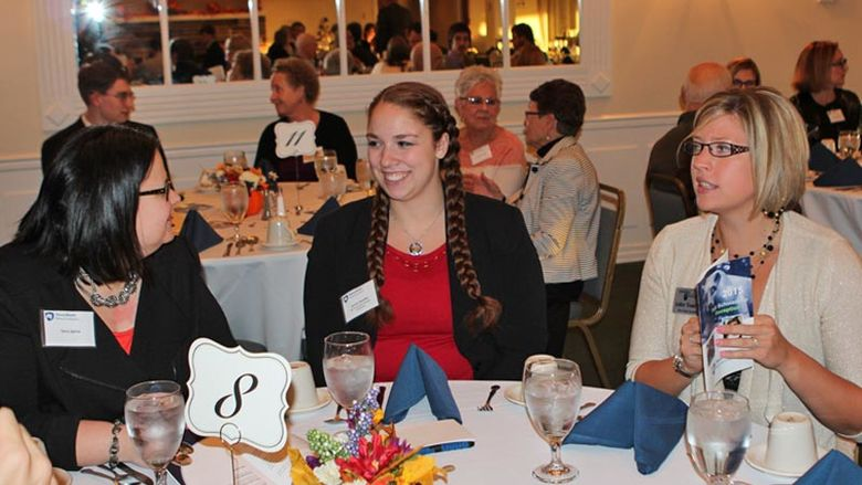 Headley and two members of the Alumni Society seated at a round table at the Scholarship Reception