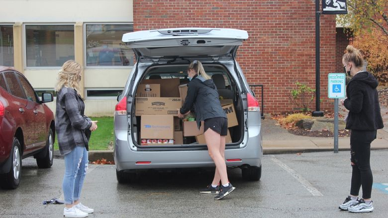Student loads food donations into car