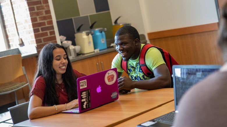 Students sit at table with laptop