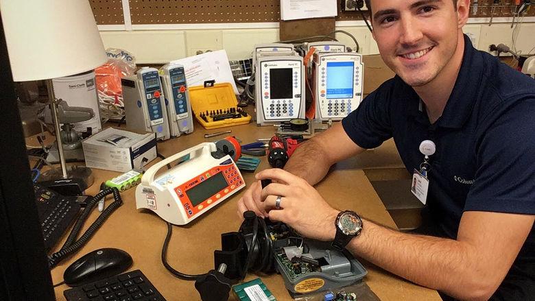 Jack DelloStritto works on hospital equipment at desk