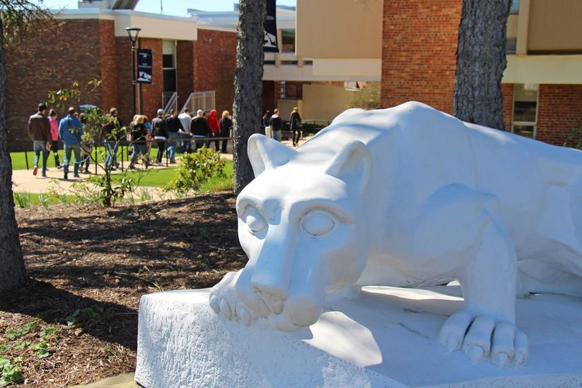 Tour group passes behind lion shrine at Penn State New Kensington