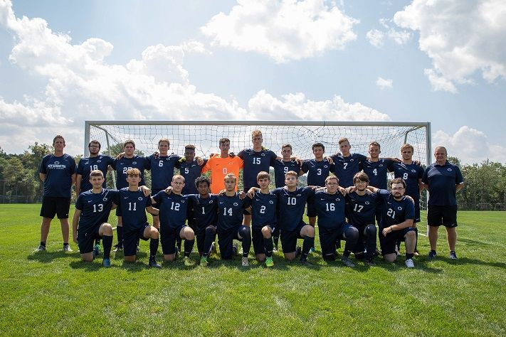 Soccer team stands in front of net for photo