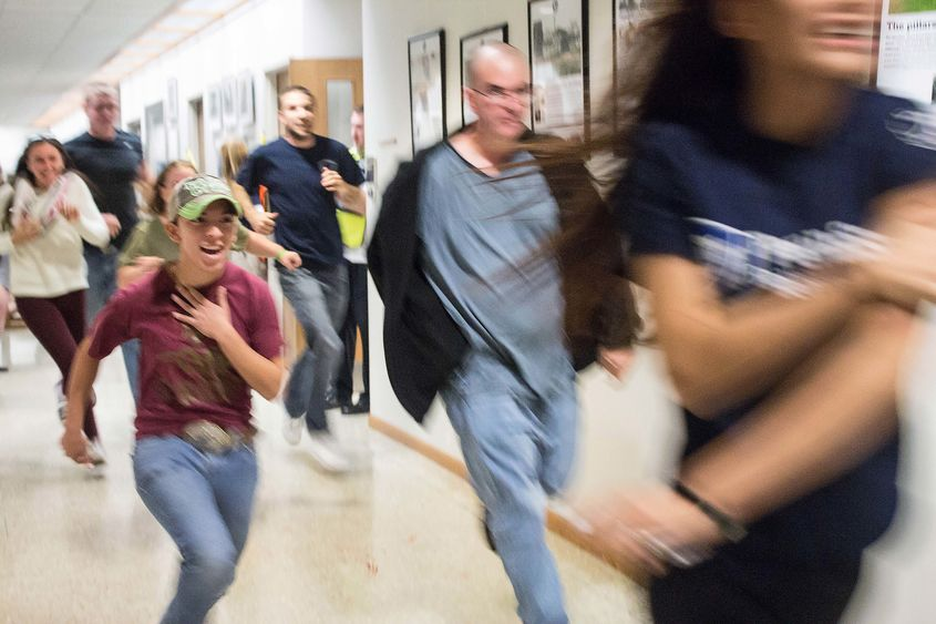 Students flee the building during an active shooter training drill at Penn State Beaver.